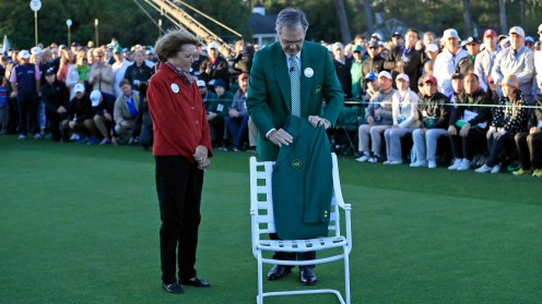 Chairman of Augusta National Golf Club and the Masters Tournament Billy Payne and Kathleen Gawthrop, the wife of Masters champion Arnold Palmer, place a Green Jacket on a chair in honor of Mr. Palmer on the No. 1 tee during Round 1 of the Masters at Augusta National Golf Club, Thursday, April 6, 2017.
